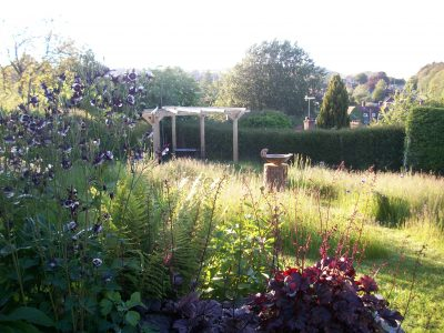 A newly planted Birch draws the eye to the end of the garden and the Downs beyond, in front is set the rustic oak pergola, so veiws