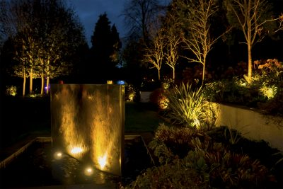 A lit water feature and garden beyond